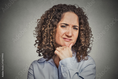 Photo Skeptic. Doubtful woman looking at you grey background