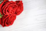 Czerwone róże w makro na drewnianej desce