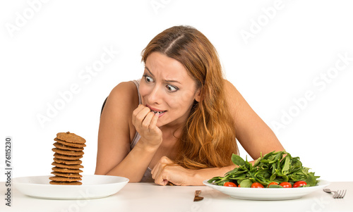 Fotografia  woman deciding whether to eat healthy food or sweet cookies