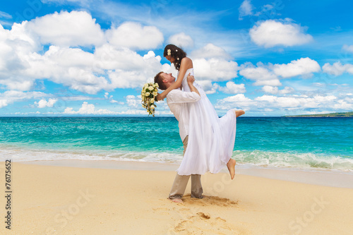 happy bride and groom having fun on a tropical beach Wallpaper Mural