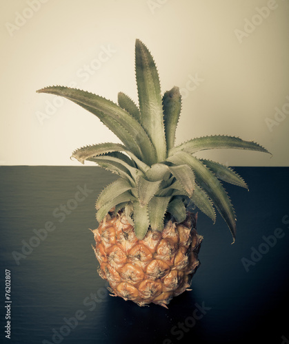 Fototapety, obrazy: Fresh whole pineapple on a black table near white wall. Toned