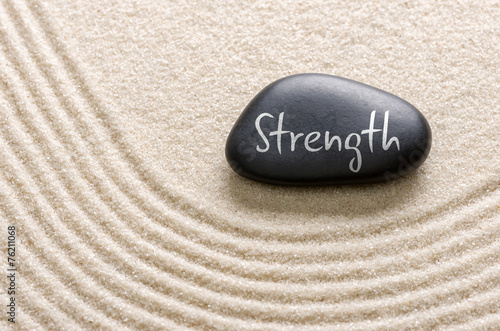 Acrylic Prints Stones in Sand Black stone with the inscription Strength