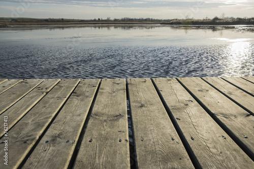 Popołudniowe słońce oświetlające pomost nad jeziorem