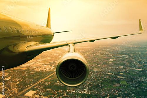 Fototapeta premium samolot lecący nad sceną miejską