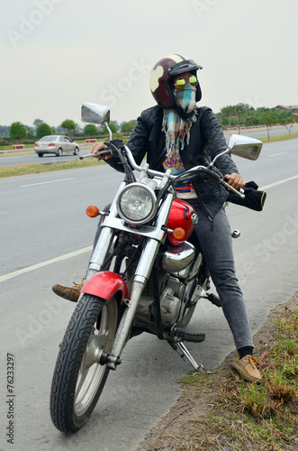 Obraz na plátne Woman riding chopper motorcycle on the way with Distance signs