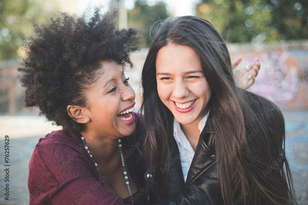 Fototapeta two multiethnic beautiful young woman black and white having fun
