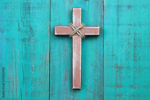 Fotografie, Obraz  Wooden cross hanging on antique teal blue wall