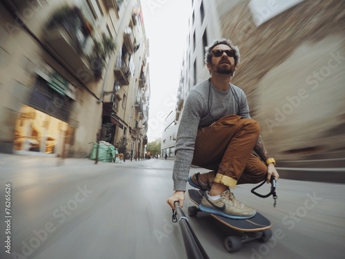 Photo  Man rides through city on skateboard
