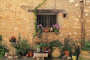 Fototapeta na wymiar window in stone rural house with flower pots, Provence