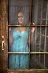 Fototapeta Young Indian Woman Gazing out Old Screen Door