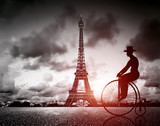 Fototapeta Eiffel Tower - Man on retro bicycle next to Effel Tower, Paris, France.