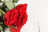 Czerwone róże na jasnej desce