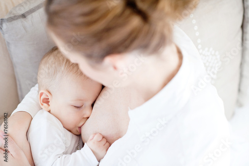 Fotomural Young mother breastfeeding the newborm baby - indoors