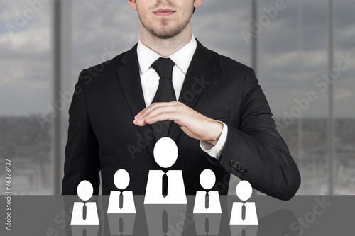 Fotografie, Obraz  businessman holding protective hand above employee staff