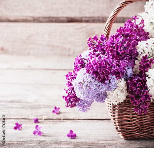 Foto op Plexiglas Lilac basket with a branch of lilac flower on a wooden background