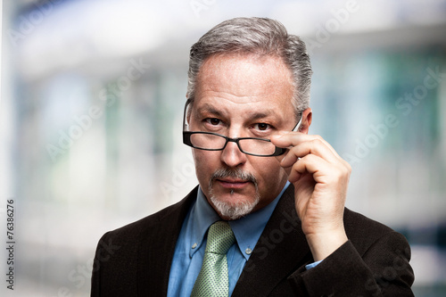 Fotografía  Mature businessman holding his eyeglasses