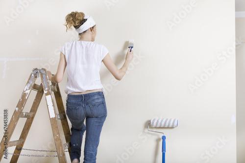 Fotografía  Frau streicht Wand auf Leiter