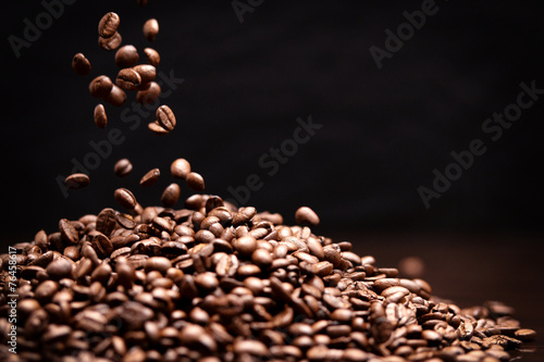 Fotobehang koffiebar High contrast image of coffee beans being dropped onto pile with