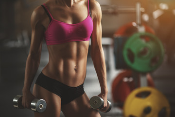 Fototapeta Brutal athletic woman pumping up muscles with dumbbells