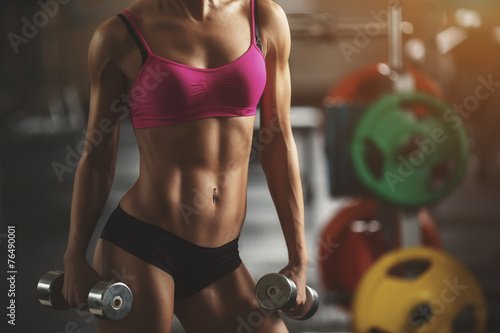 Fotografía  Brutal athletic woman pumping up muscles with dumbbells