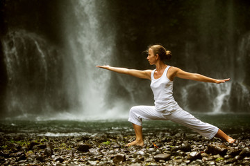 Fototapeta Sport woman meditating doing yoga between waterfalls