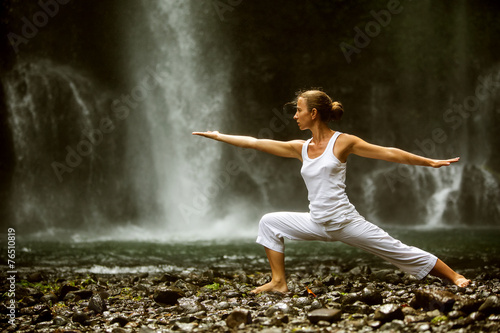 woman meditating doing yoga between waterfalls - 76510819