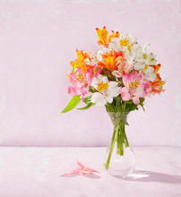 Bouquet Of Alstroemeria In Glass Vase On Light Pink Background
