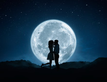 Loving Couple Kissing Against The Full Moon