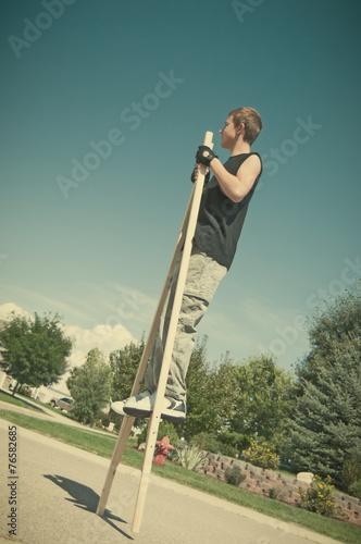 Obraz na plátne Teenage boy on stilts