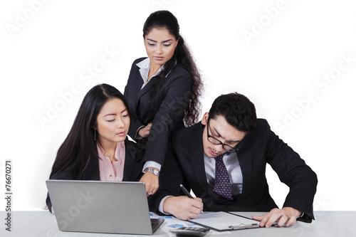 Foto  Geschäftsteam, das an Schreibtisch mit Laptop arbeitet