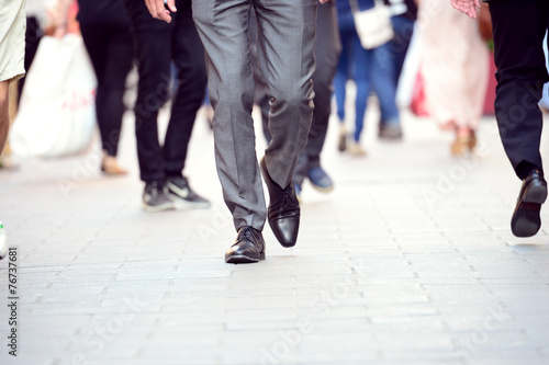 Foto  Business man in suit walking on sidewalk