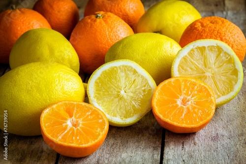 Spoed Foto op Canvas Plakjes fruit ripe mandarins and lemons cut into a rustic wooden background