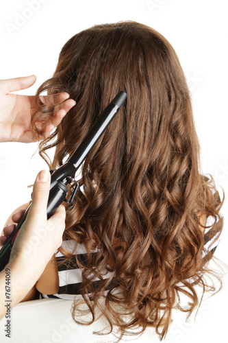 Stylist using curling iron for hair curls, close-up, isolated Poster