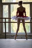 Elegancka młoda balerina stoi blisko dużego okno w tanu - 76770602