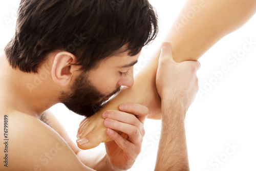 Handsome man kissing woman's feet. Fototapeta