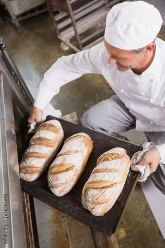Fotografie, Obraz  Baker taking tray of fresh bread out of oven