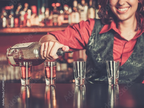 Beautiful redhead barmaid making shots Canvas Print