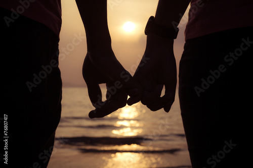 love couple holding hands fingers at sunset on the beach, valent
