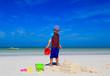 child building sandcastle on tropical beach