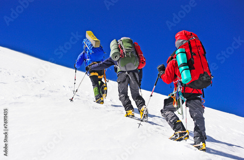Foto auf Leinwand Bergsteigen Two mountain backpackers walking on snow