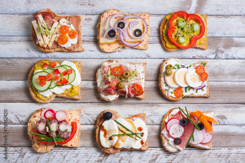 Tuinposter Snack Sandwiches on wooden background, top view