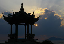 Silhouette Of A Chinese Pavilion On The Shore At Sunrise