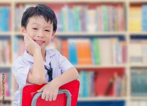 Fotografía  Asian boy student in uniform reading book in school library