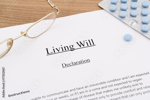 Photo living will with pills and eyeglasses on wooden table
