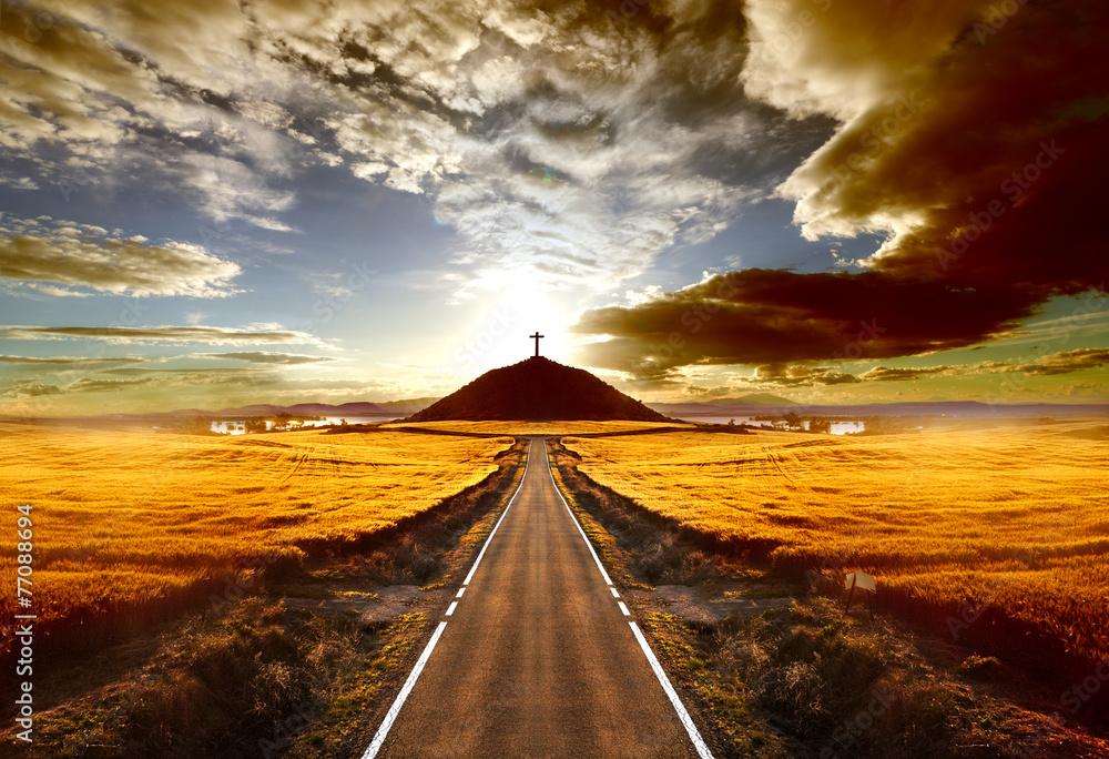 Fototapeta Aventuras y viajes por carretera.Carretera y cruz en la colina