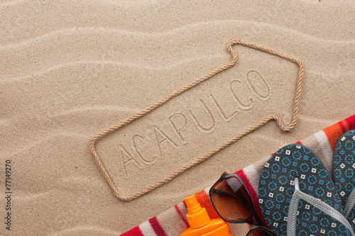 Fotografija  Acapulco pointer and beach accessories lying on the sand