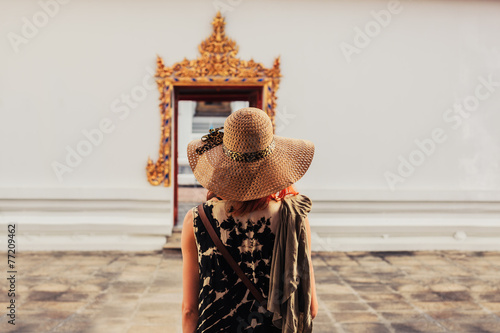 Woman looking at door to buddhist temple Wallpaper Mural