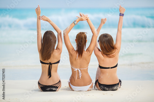 Obraz Girls in bikinis sunbathing, sitting on the beach - fototapety do salonu