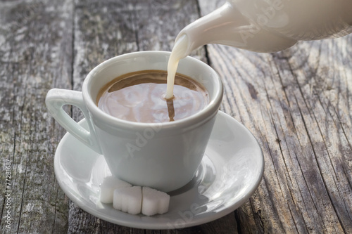 Poster Chocolate pouring milk from jug cup black coffee