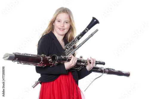 young girl holds woodwind instruments in studio Canvas Print